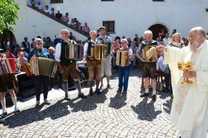 Pfarrer Matthias Oberascher segnete im Schlosshof der Wallfahrtskirche Mariastein Harmonika-Spieler und ihre Instrumente. Foto: Nageler