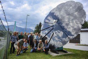 """Ein Gruppenfoto beim """"Wahrzeichen"""" der Stadtwerke Wörgl, der """"Sun Flower"""". Foto: Hubert Berger"""