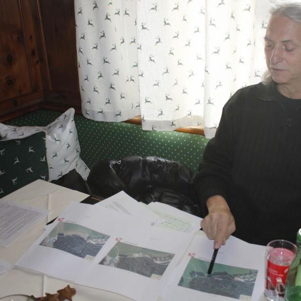 Grün-Gemeinderat Richard Götz mit Luftbildern der Fläche, auf der die illegale Deponie bestanden hatte.
