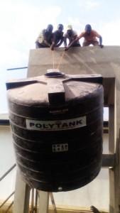 Bauarbeiter bei der Installation des 1000 Liter-Polytanks. Foto: privat