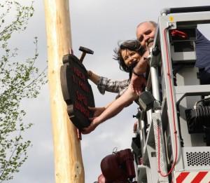 Hedi Wechner und Robert Graus beim Anbringen der Maibaumtafel. Foto: Wilhelm Maier