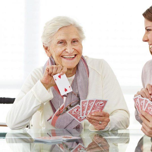Junge Frau spielt mit einer glücklichen Seniorin im Seniorenheim Karten. Foto: fotolia - Robert Kneschke