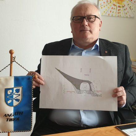 Bürgermeister Josef Haaser mit der Skizze der abgelehnten Stahlröhre zur Sanierung des Inn-Radweges. Foto: Gemeinde Angath