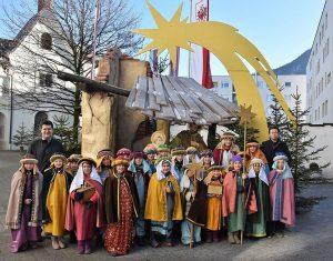 Am Dreikönigstag: Wörgler Sternsinger nach dem Gottesdienst vor der Freikrippe im Kirchhof. Foto: Heinz Werlberger